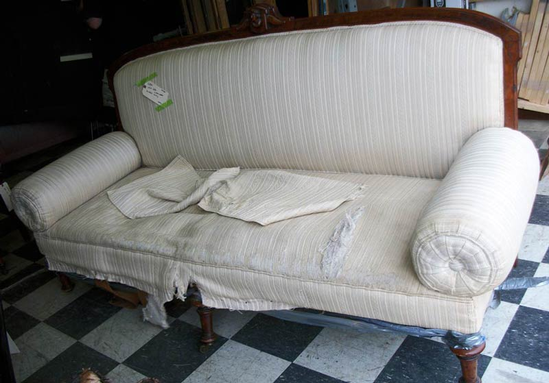 cream striped sofa with torn upholstery