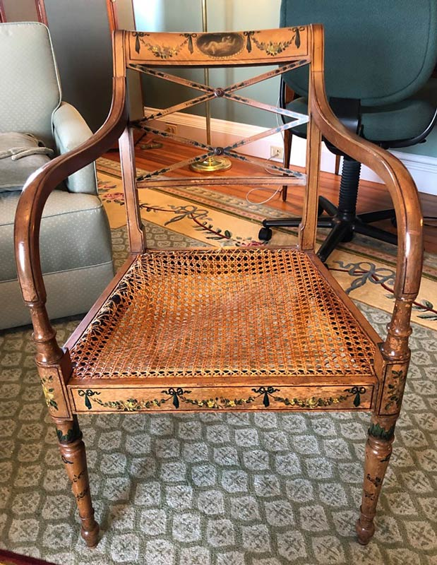 torn and warped caning in a wooden chair